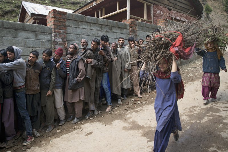 FILE - In this April 18, 2019, file photo, young Kashmiri girls carry firewood past voters queueing outside a polling station during the second phase of India's general elections, in Baba Nagri, about 44 kms. (28 miles) northeast of Srinagar, Indian controlled Kashmir. (AP Photo/ Dar Yasin, File)
