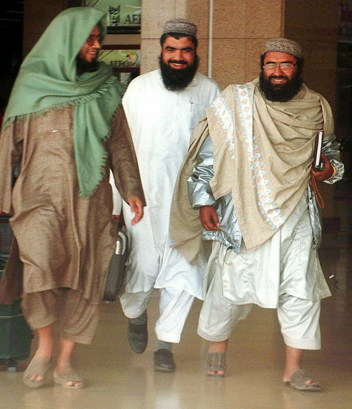 FILE - In this Jan. 22, 2000, file photo, leader of an outlawed Pakistani militant group Masood Azhar, right, walks with two unidentified people at the Karachi airport in Pakistan. (AP Photo/Athar Hussain, File)