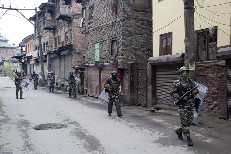 FILE - In this April 18, 2019, file photo, Indian paramilitary soldiers patrol a deserted street during the second phase of India's general elections, in Srinagar, Indian controlled Kashmir, after Kashmiri separatist leaders who challenge India's sovereignty over the disputed region called for a boycott of the vote. (AP Photo/ Dar Yasin)