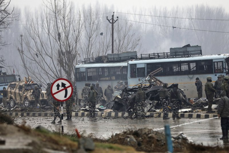 FILE - In this Feb. 14, 2019, file photo, Indian paramilitary soldiers stand by the wreckage of a bus after an explosion in Pampore, Indian-controlled Kashmir. (AP Photo/Umer Asif, File)