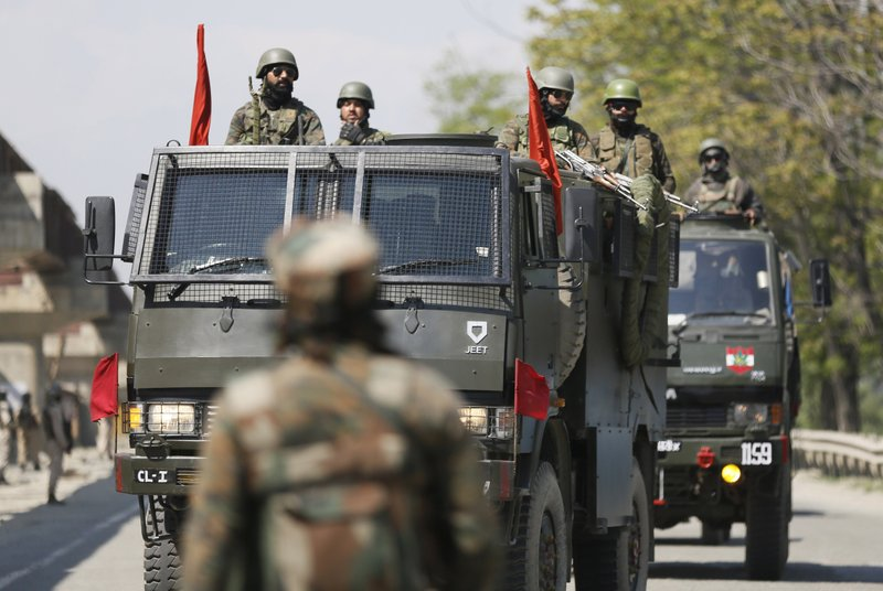 In this Sunday, April 21, 2019, photo, an Indian soldier stands guard as an army convoy moves during a biweekly ban on the movement of civilian vehicles for the safe passage of Indian security force convoy on a key highway on the outskirts of Srinagar, Indian controlled Kashmir. (AP Photo/Mukhtar Khan)