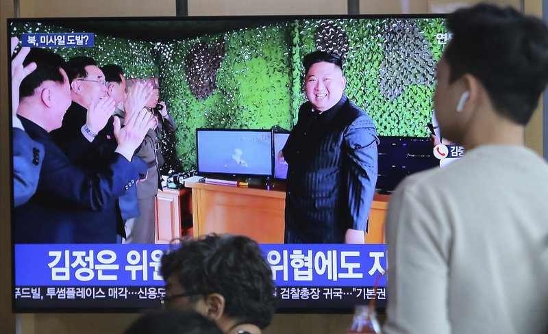 FILE - In this May 5, 2019, file photo, people watch a TV showing a photo of North Korean leader Kim Jong Un during a news program reporting North Korea's missile launch, at the Seoul Railway Station in Seoul, South Korea. (AP Photo/Ahn Young-joon, File)