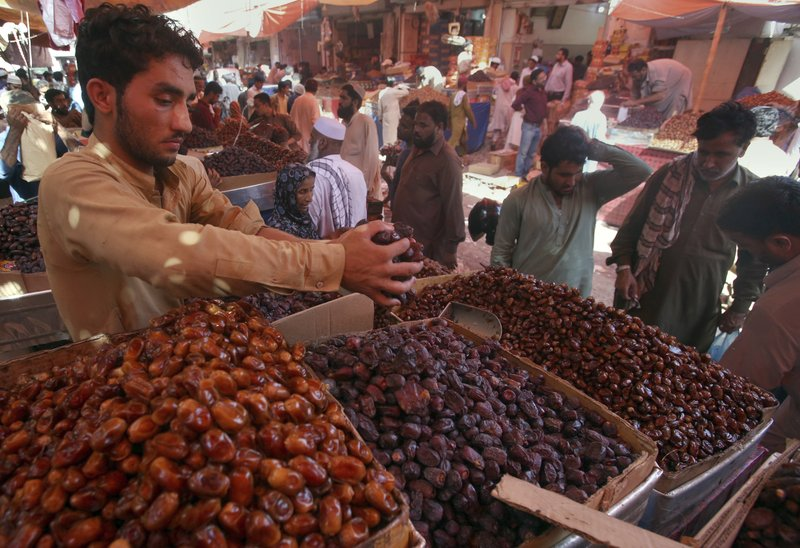 FILE - In this Sunday, May 5, 2019 file photo, people buy dates, a favorite food for Muslims' fasting month of Ramadan, at a wholesale market in Karachi. (AP Photo/Fareed Khan, File)