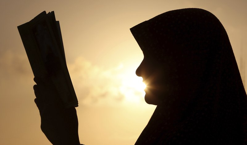 FILE - In this July 4, 2014 file photo, a Palestinian girl reads the Quran, Islam's holy book during Ramadan, at sunset in Gaza City. (AP Photo/Hatem Moussa, File)