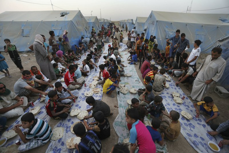 FILE - In this June 29, 2014 file photo, displaced Iraqi citizens gather for a communal meal to break their fast during the first day of the Islamic holy month of Ramadan, at an encampment for displaced Iraqis, in the Khazer area outside Irbil, northern Iraq. (AP Photo/Hussein Malla, File)