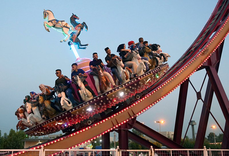 FILE - In this June 16, 2018 file photo, people take a ride at an amusement park during Eid al-Fitr celebrations, that mark the end of the Muslim holy fasting month of Ramadan, in Baghdad, Iraq. (AP Photo/Karim Kadim, File)