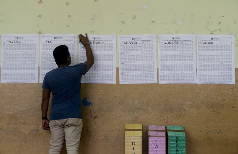 An electoral worker participates in the manual counting of ballots after polling stations closed for the general election in Panama City, Sunday, May 5, 2019. (AP Photo/Arnulfo Franco)
