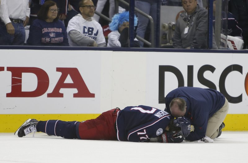 Columbus Blue Jackets athletic trainer Mike Vogt, right, tends to Josh Anderson after he was hit by Boston Bruins' Charlie McAvoy during the second period of Game 6 of an NHL hockey second-round playoff series Monday, May 6, 2019, in Columbus, Ohio. (AP Photo/Jay LaPrete)