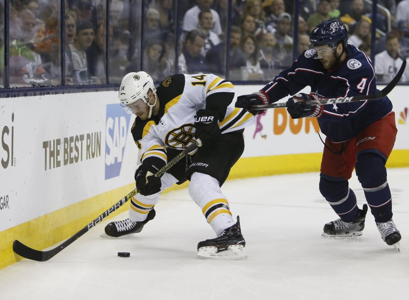 Boston Bruins' Chris Wagner, left, carries the puck behind the net as Columbus Blue Jackets' Scott Harrington defends during the first period of Game 6 of an NHL hockey second-round playoff series Monday, May 6, 2019, in Columbus, Ohio. (AP Photo/Jay LaPrete)