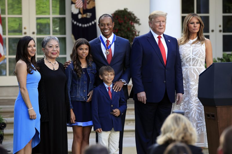 President Donald Trump, first lady Melania Trump and Tiger Woods pose for a picture with, from left, Woods' girlfriend Erica Herman, his mother Kultida Woods, children Sam Alexis Woods and Charlie Axel Woods during a ceremony awarding Woods with the Presidential Medal of Freedom in the Rose Garden of the White House in Washington, Monday, May 6, 2019. (AP Photo/Manuel Balce Ceneta)