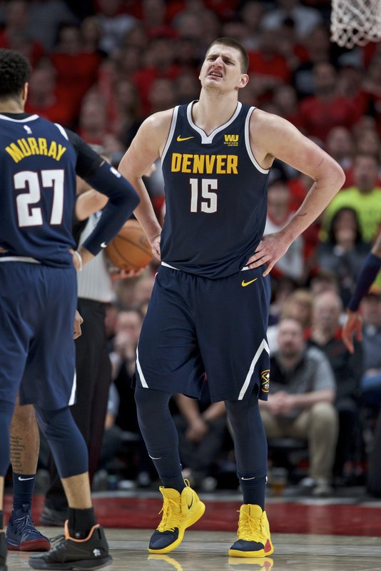 Denver Nuggets center Nikola Jokic grimaces as he walks off the court against the Portland Trail Blazers during the first half of Game 4 of an NBA basketball second-round playoff series, Sunday, May 5, 2019, in Portland, Ore. (AP Photo/Craig Mitchelldyer)