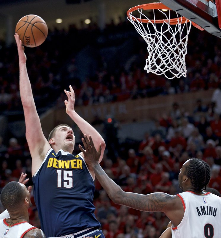 Denver Nuggets center Nikola Jokic, left, shoots over Portland Trail Blazers forward Al-Farouq Aminu during the first half of Game 4 of an NBA basketball second-round playoff series Sunday, May 5, 2019, in Portland, Ore. (AP Photo/Craig Mitchelldyer)