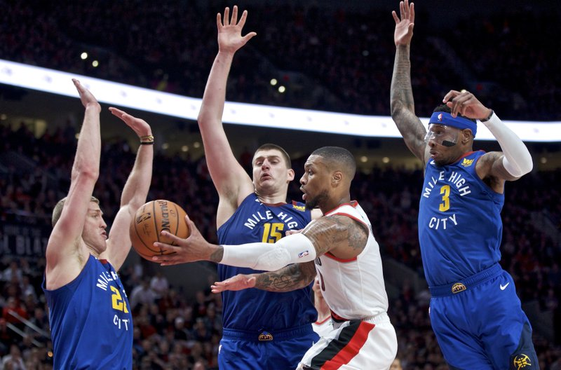 Portland Trail Blazers guard Damian Lillard, center, passes the ball away from Denver Nuggets forward Mason Plumlee, left, center Nikola Jokic, second from left, and forward Torrey Craig, right, during overtime of Game 3 of an NBA basketball second-round playoff series Friday, May 3, 2019, in Portland, Ore. (AP Photo/Craig Mitchelldyer)