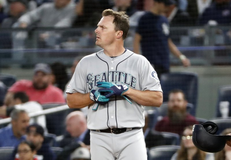 Seattle Mariners' Jay Bruce looks at the stats as he removes his batting gloves after grounding out with the bases loaded in the fifth inning of a baseball game against the New York Yankees, Monday, May 6, 2019, in New York. (AP Photo/Kathy Willens)