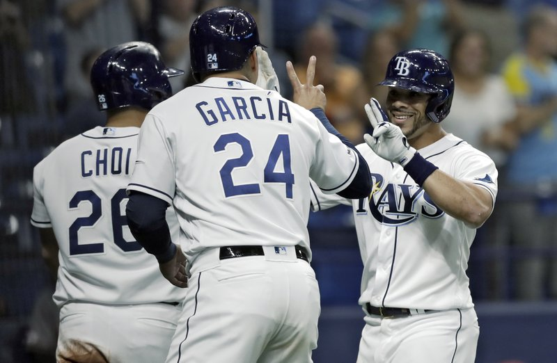 Tampa Bay Rays' Tommy Pham celebrates with Avisail Garcia (24) and Ji-Man Choi (26) after hitting a grand slam off Arizona Diamondbacks starting pitcher Merrill Kelly during the second inning of a baseball game Monday, May 6, 2019, in St. (AP Photo/Chris O'Meara)