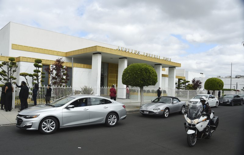 Cars file into the Angelus Funeral Home parking lot for a memorial service for the late film director John Singleton, Monday, May 6, 2019, in Los Angeles. (AP Photo/Chris Pizzello)
