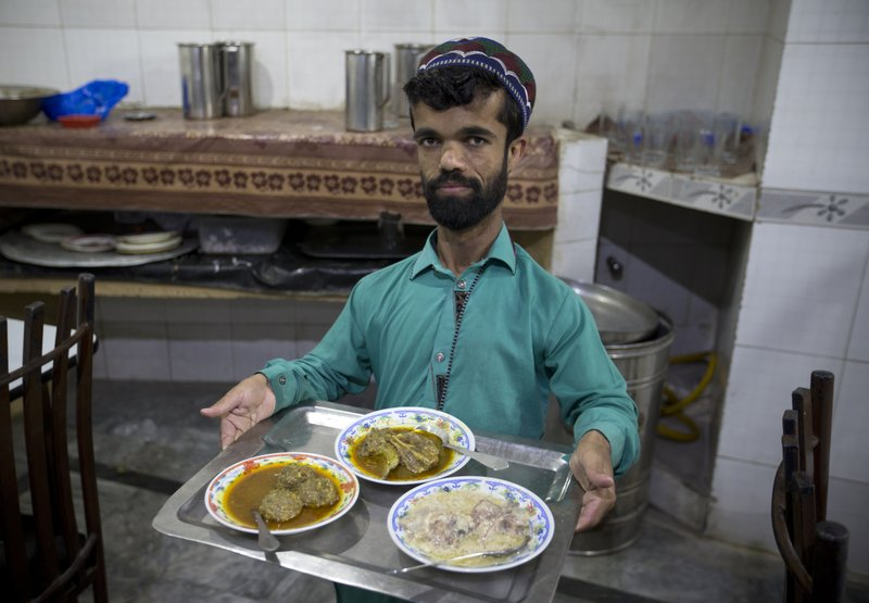 In this Friday, May 3, 2019 photo, Rozi Khan, a 26-year-old Pakistani who shares a resemblance to the U. (AP Photo/B.K. Bangash)