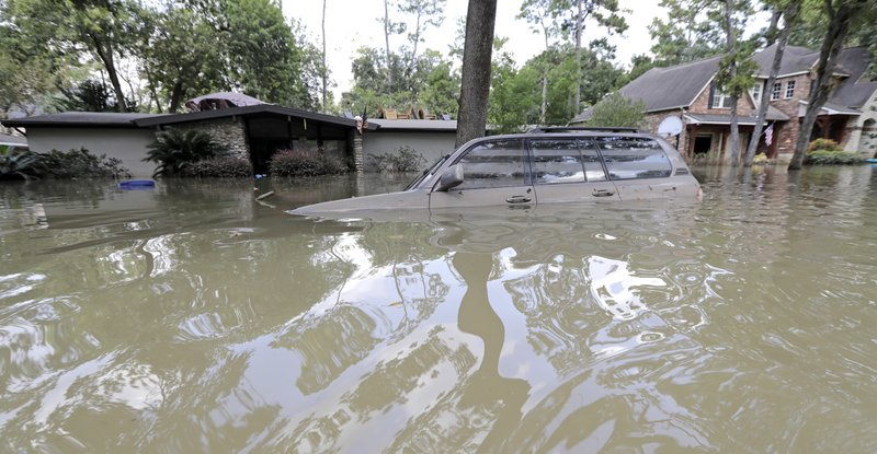 FILE - In this Sept. 4, 2017 file photo, a car is submerged in a current of floodwater in the aftermath of Hurricane Harvey near the Addicks and Barker Reservoirs in Houston. (AP Photo/David J. Phillip, File)