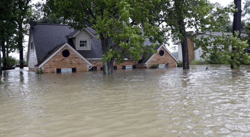 FILE - In this Aug. 28, 2017 file photo, is a home surrounded by floodwaters from Tropical Storm Harvey in Spring, Texas. (AP Photo/David J. Phillip, File)