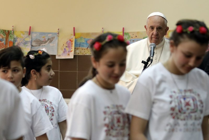 Pope Francis looks at children who performed a song for him during his visit to a refugee center on the outskirts of Sofia, Bulgaria, Monday, May 6, 2019. (AP Photo/Alessandra Tarantino)