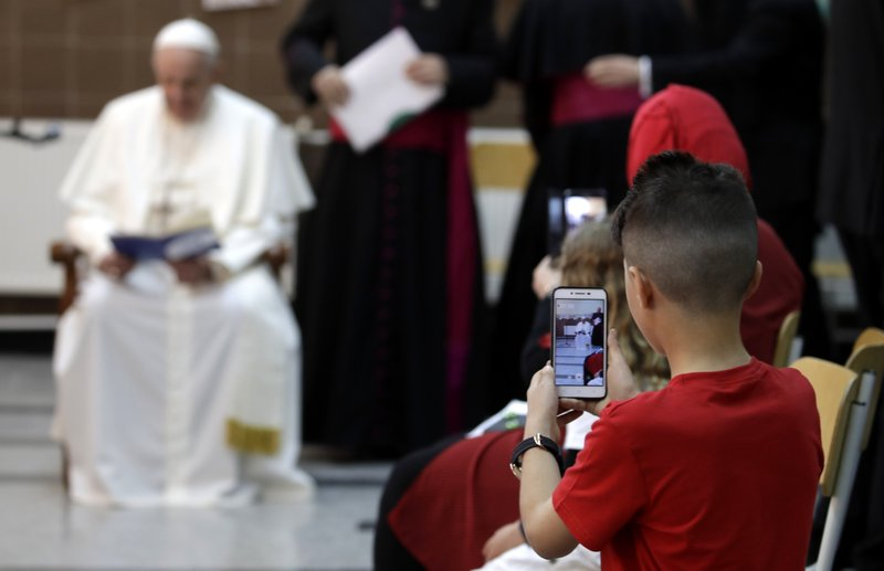A child uses his phone to film Pope Francis during his visit to a refugee center on the outskirts of Sofia, Bulgaria, Monday, May 6, 2019. (AP Photo/Alessandra Tarantino)