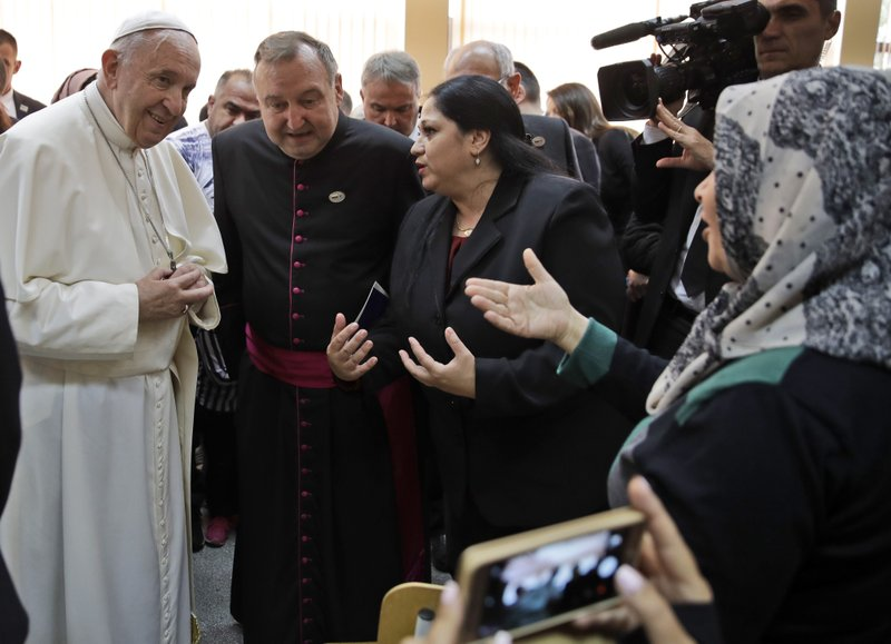 Pope Francis speaks with a woman from Syria, at right wearing a scarf on her head, during his visit to a refugee center on the outskirts of Sofia, Bulgaria, Monday, May 6, 2019. (AP Photo/Alessandra Tarantino)