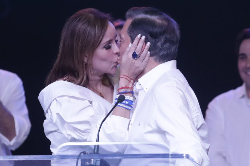 Presidential candidate Laurentino Cortizo, right, with the Democratic Revolutionary Party, is kissed by his wife Yazmin during a meeting with supporters in Panama City, Monday, May 6, 2019. (AP Photo/Arnulfo Franco)