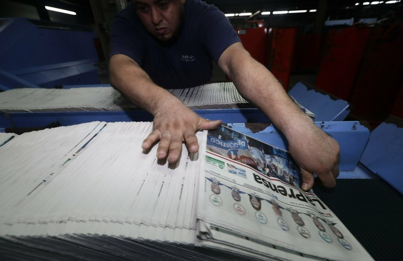Recently printed copies of La Prensa newspaper show photos of the presidential candidates who ran in the previous day's election, with the Spanish headline