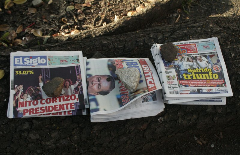 Rocks sit on stacks of a street vendor's newspapers that carry headlines announcing the winner of the previous day's presidential election in Panama City, Monday, May 6, 2019. (AP Photo/Juan Zamorano Jr.)