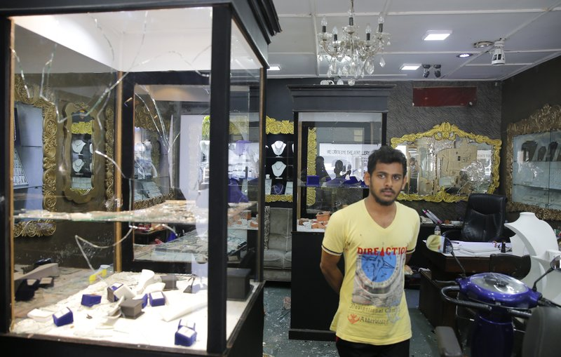 A Sri Lankan Muslim man stands in a vandalized jewelry showroom following overnight clashes with Christians in Poruthota, a village in Negombo, about 35 kilometers North of Colombo, Sri Lanka, Monday, May 6, 2019. (AP Photo/Eranga Jayawardena)