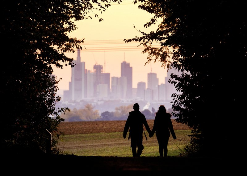 FILE - In this Oct. 21, 2018, file photo, a couple walks through a forest with the Frankfurt skyline in background near Frankfurt, Germany. (AP Photo/Michael Probst, File)