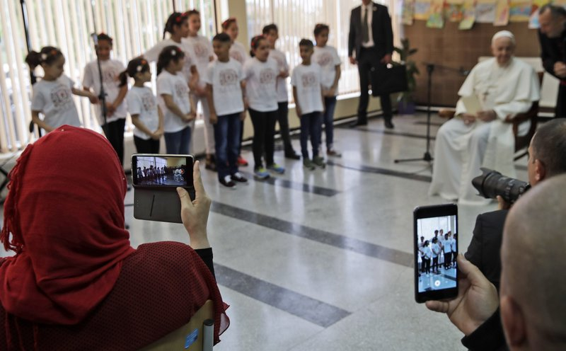Refugees film with their phones Pope Francis listening to group of children singing for him during his visit to a refugee center on the outskirts of Sofia, Bulgaria, Monday, May 6, 2019. (AP Photo/Alessandra Tarantino)