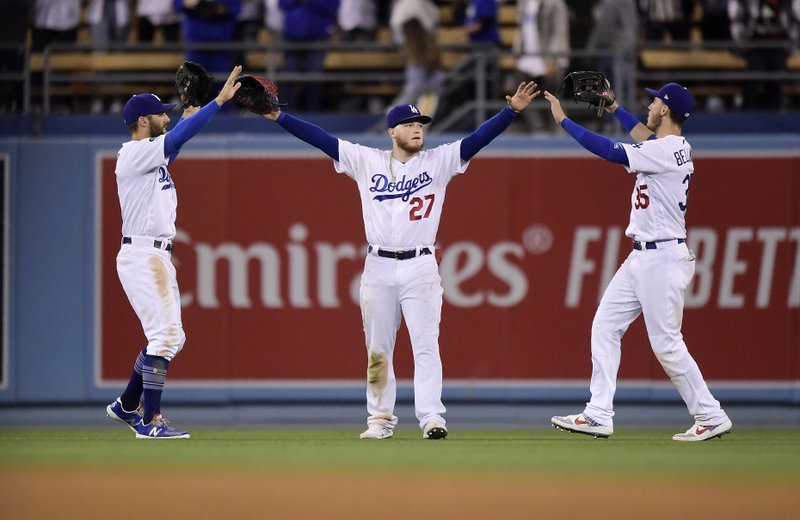 Los Angeles Dodgers' Chris Taylor, left, Alex Verdugo, center, and Cody Bellinger congratulate each other after the Dodgers defeated the Atlanta Braves 5-3 in a baseball game, Monday, May 6, 2019, in Los Angeles. (AP Photo/Mark J. Terrill)