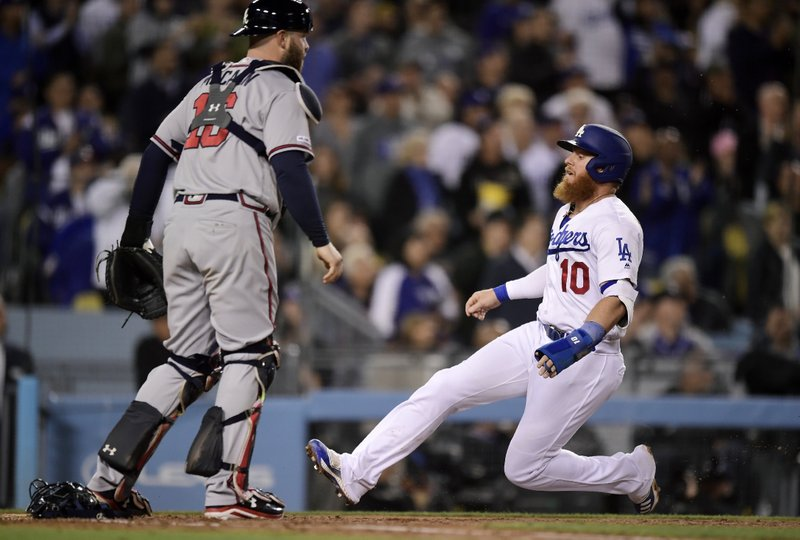 Los Angeles Dodgers' Justin Turner, right, scores on a single by Chris Taylor as Atlanta Braves catcher Brian McCann stands at the plate during the third inning of a baseball game, Monday, May 6, 2019, in Los Angeles. (AP Photo/Mark J. Terrill)