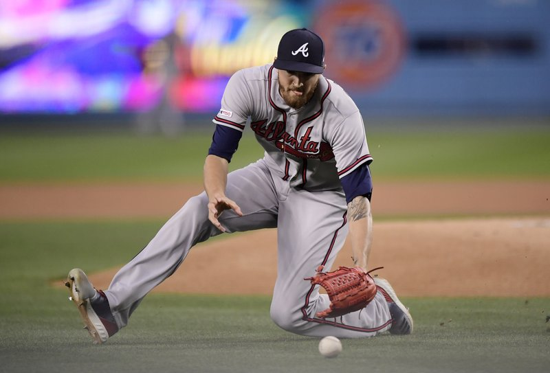 Atlanta Braves starting pitcher Kevin Gausman fields a ball hit by Los Angeles Dodgers' Cody Bellinger for a bunt-single during the first inning of a baseball game Monday, May 6, 2019, in Los Angeles. (AP Photo/Mark J. Terrill)