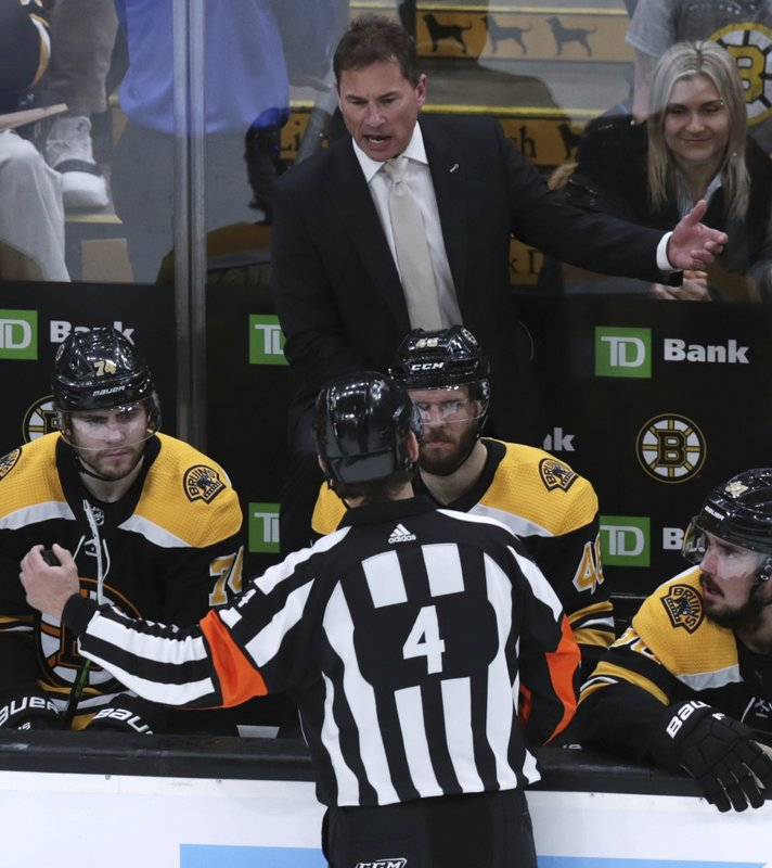 Boston Bruins head coach Bruce Cassidy, top, argues with referee Wes McCauley (4) after video replay on a