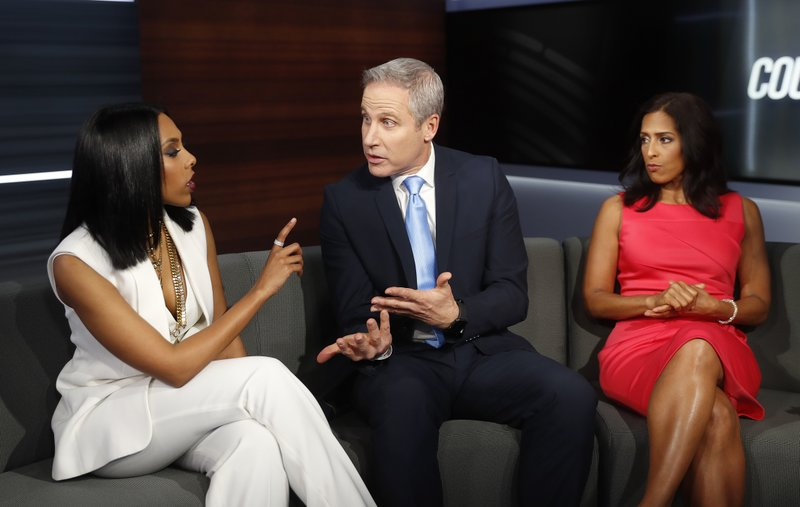 In this Thursday, May 2, 2019, photo, Court TV anchors from left, Yodit Tewolde, Vinnie Politan and Seema Iyer discuss a court case as they rehearse on the set, in Atlanta. (AP Photo/John Bazemore)