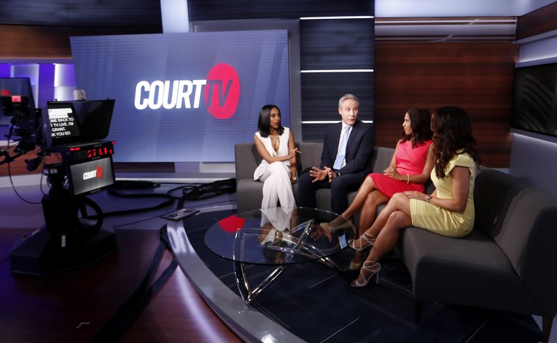 In this Thursday, May 2, 2019, photo, Court TV anchors from left, Yodit Tewolde, Vinnie Politan , Seema Iyer and Julie Grant discuss a court case as they rehearse on the set, in Atlanta. (AP Photo/John Bazemore)