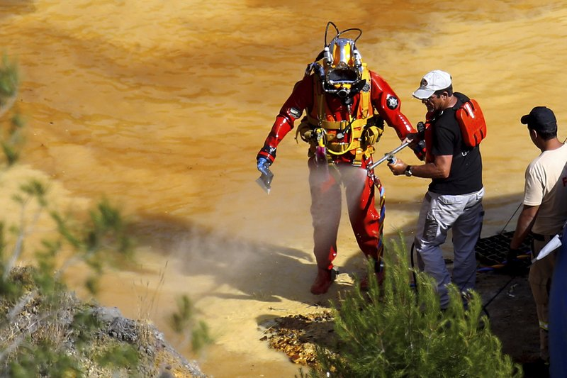 A man sprays water as clean the diver after a dive in a toxic man-made lake during a search for a third suitcase near the village of Mitsero outside of the capital Nicosia, Cyprus, Monday, May 6, 2019. (AP Photo/Petros Karadjias)