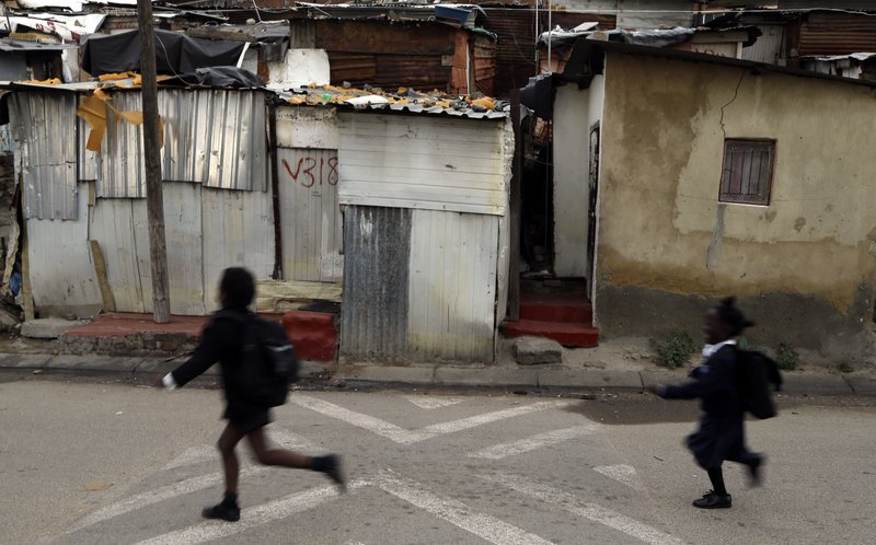 FILE - In this April 22, 2015, file photo, children run to school in Alexandra township in Johannesburg, South Africa. (AP Photo/Themba Hadebe, File)