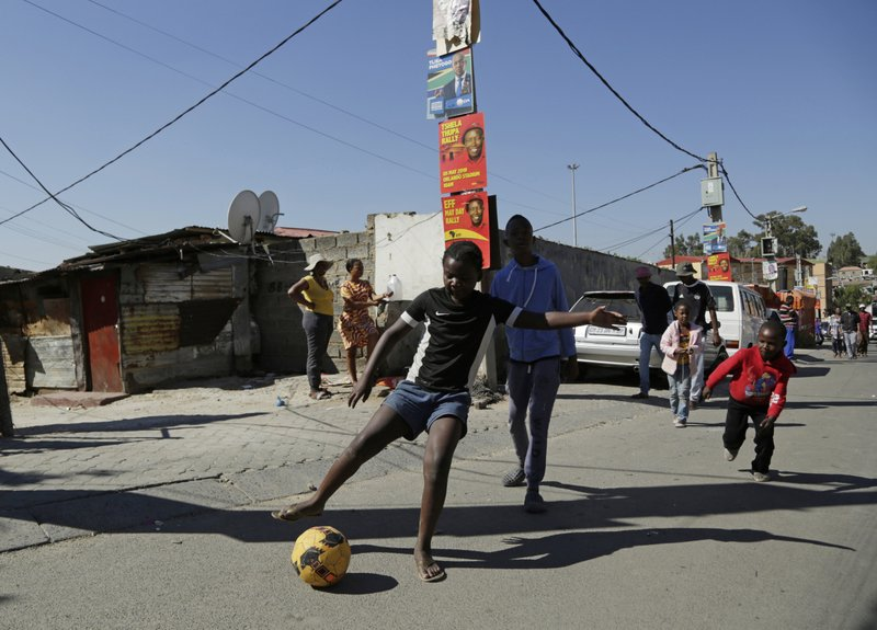 In this May 1, 2019, photo, children play football in a main street in Alexandra Township of Johannesburg. (AP Photo/Themba Hadebe)