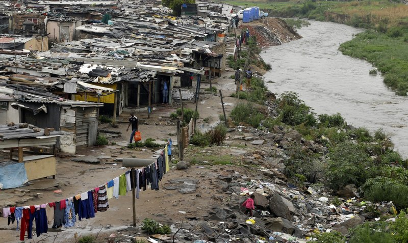 FILE - In this Nov. 11, 2014, file photo, a man walks along an informal settlement as a young girl plays next to the polluted Jukskei River in Alexandra, northern Johannesburg, South Africa. (AP Photo/Themba Hadebe, File)