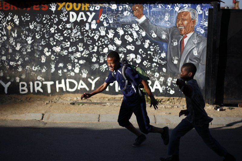 FILE - In this June 13, 2013, file photo, students walk in front of a mural outside the former home of Nelson Mandela, the first black president of South Africa, in Alexandra township in Johannesburg. (AP Photo/Jerome Delay, File)