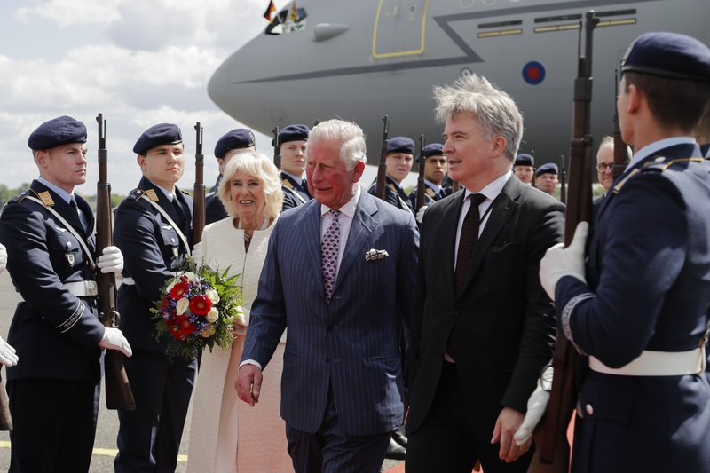 Britain's Prince Charles, center, the Prince of Wales and his wife Camilla, Duchess of Cornwall, left, are welcomed by Britain's ambassador in Germany Sebastian Wood, right, during arriving for a four days visit in Germany, at the airport Tegel in Berlin, Germany, Tuesday, May 7, 2019. (AP Photo/Markus Schreiber, Pool)