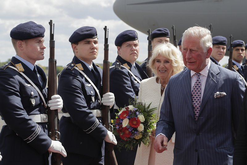 Camilla, Duchess of Cornwall, center, and Britain's Prince Charles, right, the Prince of Wales review the honour guards as they arrive for a four days visit in Germany, at the airport Tegel in Berlin, Tuesday, May 7, 2019. (AP Photo/Markus Schreiber, Pool)