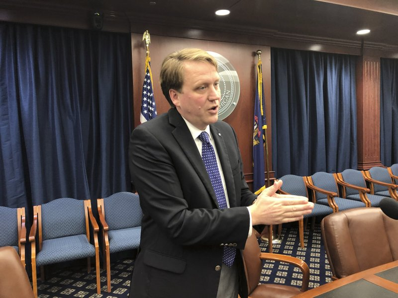 Sen. Aric Nesbitt, a Lawton Republican, speaks with reporters following a Senate committee's party-line vote in favor of his bill that would end a requirement that drivers have unlimited medical coverage through their car insurer on Tuesday, May 7, 2019, in Lansing, Mich. (AP Photo/David Eggert)