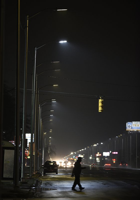 In the Thursday, May 2, 2019 photo, a pedestrian crosses Gratiot Street at Outer Drive East under a bright streetlight flanked by dimmer streetlights in Detroit. (Clarence Tabb Jr./Detroit News via AP)