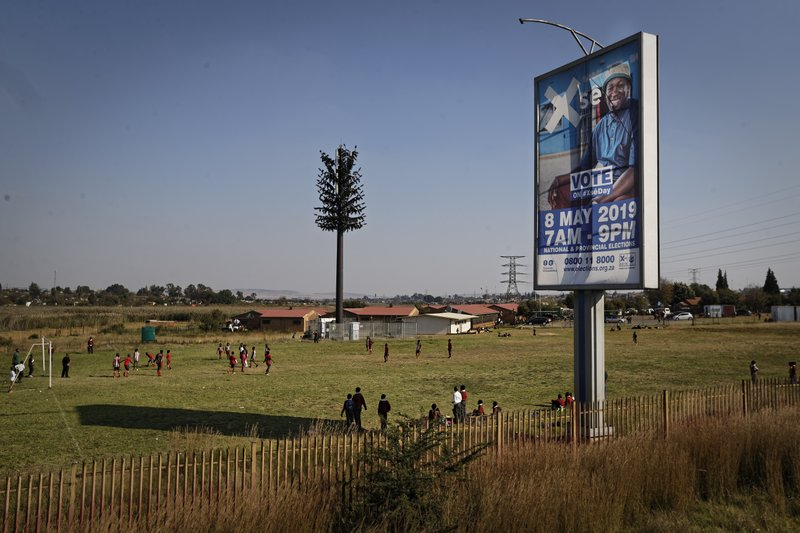 Schoolchildren play football in the afternoon next to a billboard from the Independent Electoral Commission of South Africa (IEC) encouraging people to vote, in Soweto, Johannesburg, South Africa Tuesday, May 7, 2019. (AP Photo/Ben Curtis)