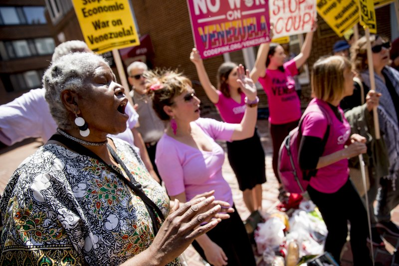 U.S. activist Medea Benjamin, co-founder of the anti-war group Code Pink, right, and others, sing together outside the Venezuelan Embassy in Washington, Thursday, May 2, 2019. (AP Photo/Andrew Harnik)