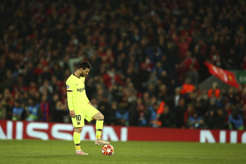 Barcelona's Lionel Messi keeps the ball as Liverpool's Divock Origi celebrates scoring his side's 4th goal during the Champions League semifinal, second leg, soccer match between Liverpool and FC Barcelona at the Anfield stadium in Liverpool, England, Tuesday, May 7, 2019. (AP Photo/Dave Thompson)